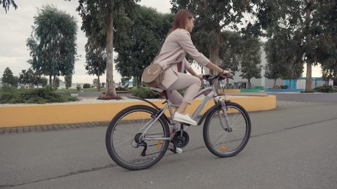 Side view shot of a lovely girl riding a bycicle in a city. Nice woman enjoying quiet ride in town, beautiful view.