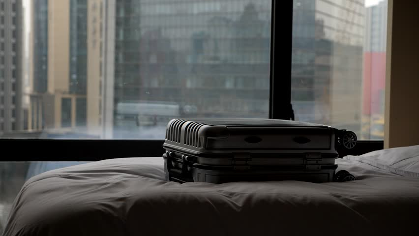 Medium size plastic suitcase lie on bed against window, blurred city buildings seen outside on background. End of short duty trip abroad, someone ready to check-out from hotel | Shutterstock HD Video #1024305953