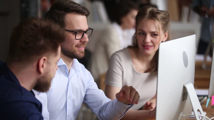 Three colleagues working together discuss computer project teamwork, business people corporate team coworkers cooperating laughing at workplace, smiling employees group having fun talking in office | Shutterstock HD Video #1024307063
