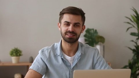 Confident young businessman speaker looking talking to camera recording training, male coach teacher trainer speaking shooting video reportage vlog tutorial advertising business services with laptop