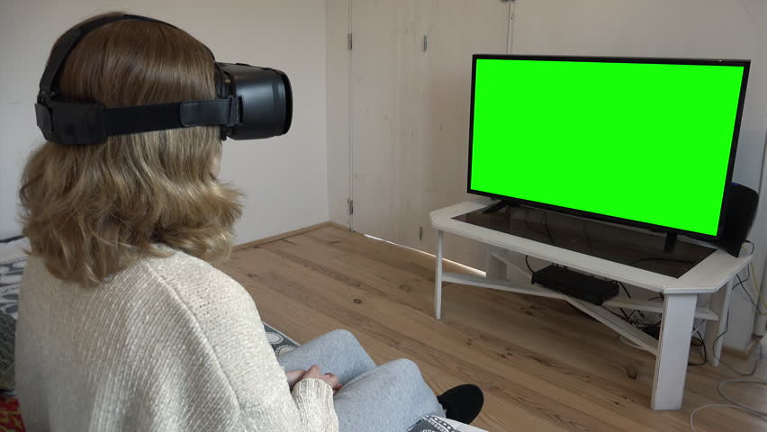 Virtual Reality Girl TV Green Screen Background Television. Young woman using augmented reality headset in front of a green screen television. #1024335173