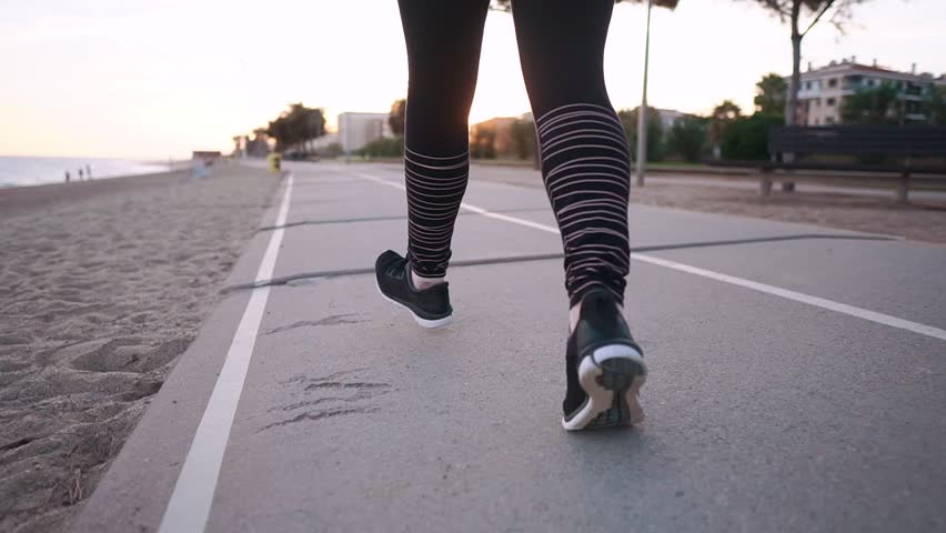 Townswoman is jogging outdoors in evening time in city streets. Close-up of her legs, training near sea shore, keeping fit #1024345343
