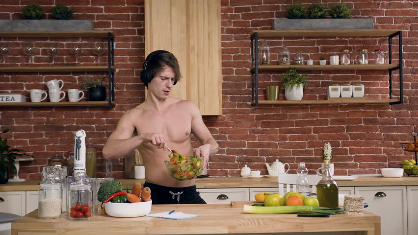 Funny fit man with naked torso listening music in the headphone and dancing while mixing healthy salad at home in the kitchen.   Shutterstock HD Video #1024385273