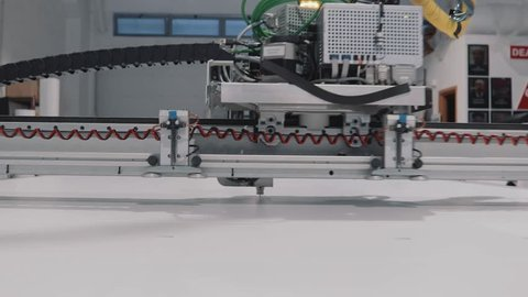 A robotic arm,ing while processing a large scale panel. Details from a big, professional, CNC printer. Motion blur, highlighting the advances and progress in the engineering and technology fields.