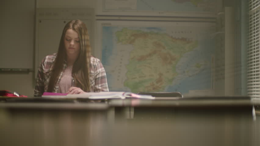 Female student in classroom surrounded by textbooks writes in her notebook working on school work in a classroom setting with map behind her and desks in the foreground. Filmed with Arri Alexa Mini | Shutterstock HD Video #1024494353