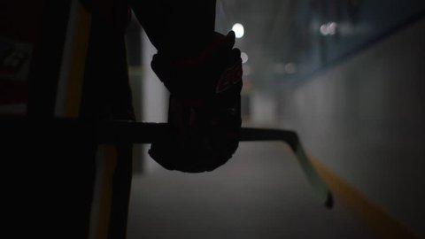 Silhouette of hockey player walks from dressing room down long corridor hallway in hockey arena twirling stick. Filmed with Arri Alexa Mini