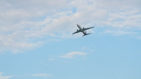 Passenger airplane takes off against the blue sky with clouds.