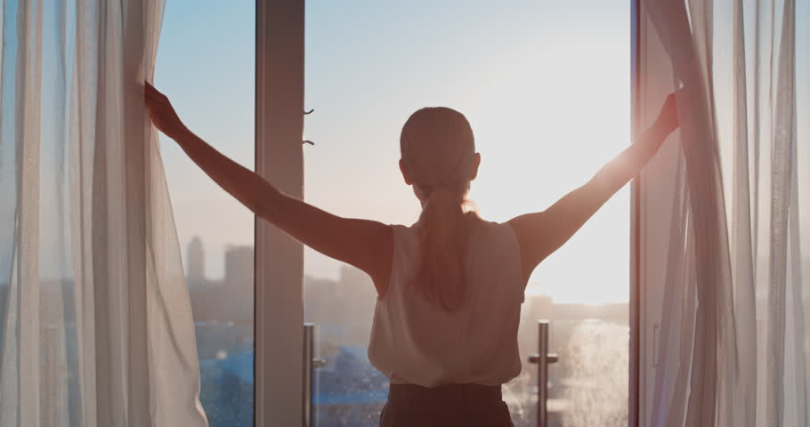business woman opening curtains in hotel room looking out window at fresh new day successful independent female planning ahead at sunrise #1024548083