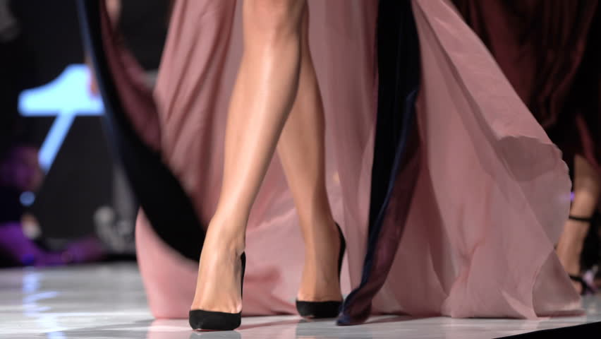 Female models walk the runway in different dresses during a Fashion Show. Fashion catwalk event showing new collection of clothes. Legs and shoes only. 4k footage. Unrecognizable people.