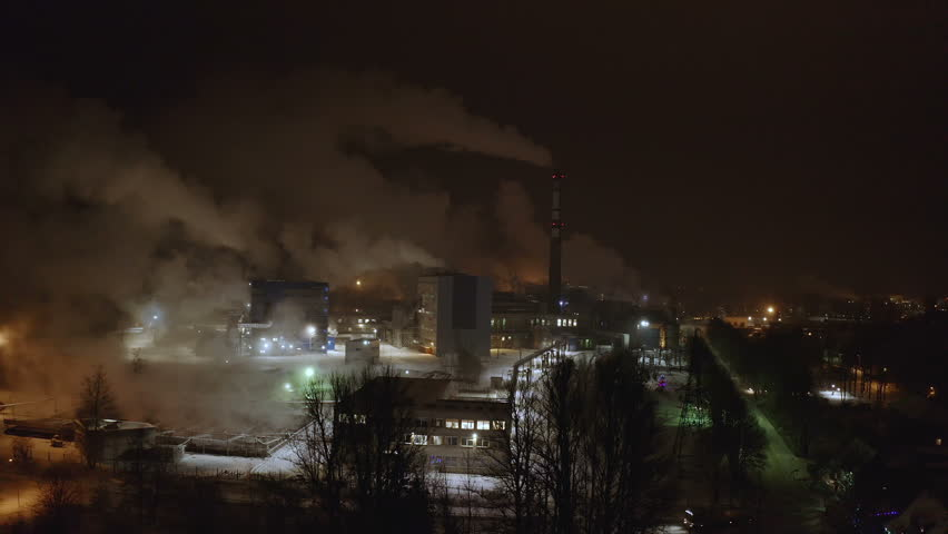 Closer look of the smoke on the air at night from the papermill factory in the city
