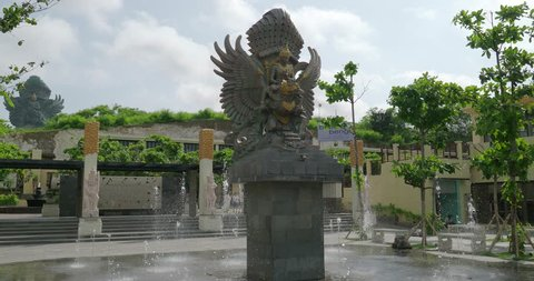 Bali, IDN, 12.10.18, Garuda Wisnu Kencana GWK Bali statue with fountain  / Garuda Wisnu Kencana GWK Bali statue with fountain and background monument at sunny day with blue sky and clouds