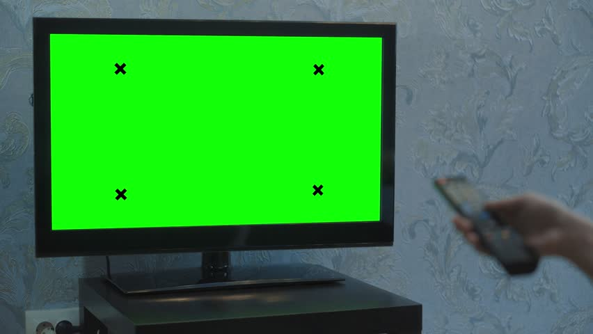 A Female hand switches channels on a TV with a green screen. TV stands on a small black table. Monitor in a room with blue wallpaper. | Shutterstock HD Video #1024603793