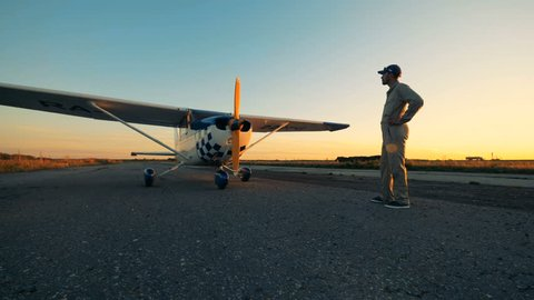 Male aviator looks at his light airplane, side view.