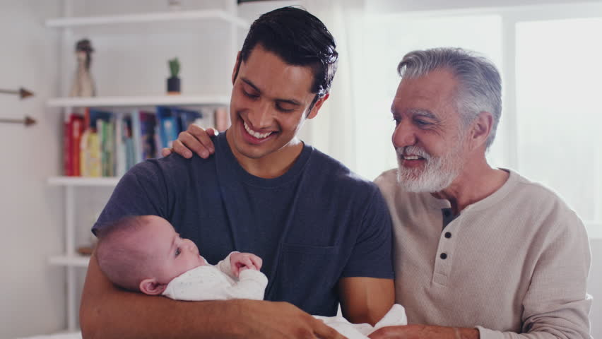 Proud Hispanic father holding his four month old son at home, with grandfather beside them, close up | Shutterstock HD Video #1024667303