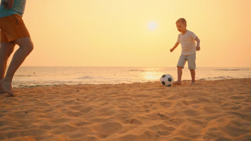 Father and son playing together with ball in football on the beach under sunset background #1024669733