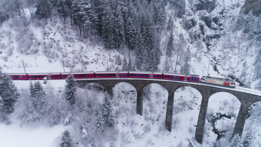 Viaduct and Train at Winter Day in Swiss Alps. Snowing. Switzerland. Aerial View. Drone Flies Forward and Downward | Shutterstock HD Video #1024700573