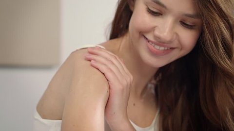 Young woman applying body lotion at morning. Close up of woman body care at home. Portrait of woman applying moisturizer cream on neck. Natural skin care