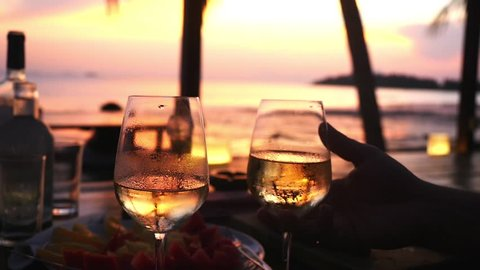 Couple takes two glasses in their hands with white wine against the sunset at the sea. slow motion, 1920x1080
