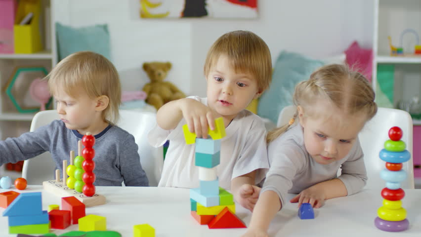 Funny little boy making toy tower with colorful blocks, getting excited and slapping it while playing with friends at table in kindergarten | Shutterstock HD Video #1024772843