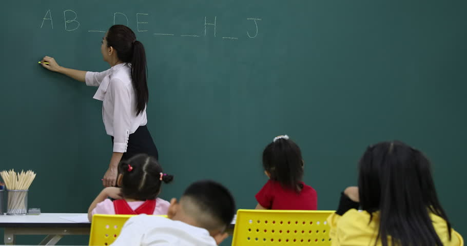 In English class, Asian teacher writes fill in the blanks game on green board, to play with her students  | Shutterstock HD Video #1024794893