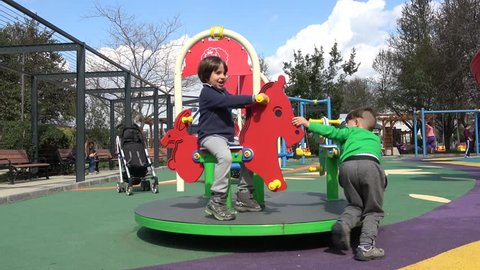 Akarca Park, Fethiye, Turkey - 23d of February 2019: 4K Two boys play on merry-go-round on the children playground