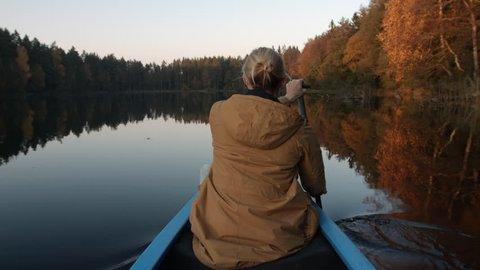 Female hiker paddle a canoe on lake at sunset