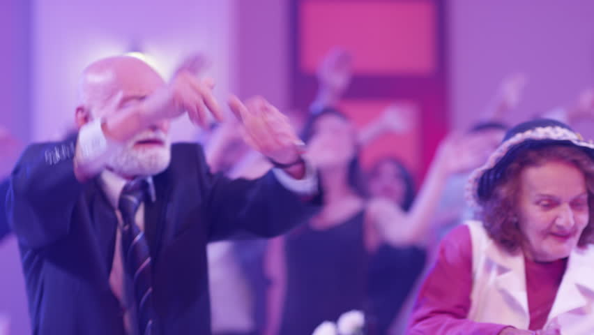 Stylish elderly couple having fun dancing at a colorful party . Sweet senior couple smiling and partying during party . Active retirement . Shot on RED HELIUM Cinema Camera in slow mo | Shutterstock HD Video #1024895603
