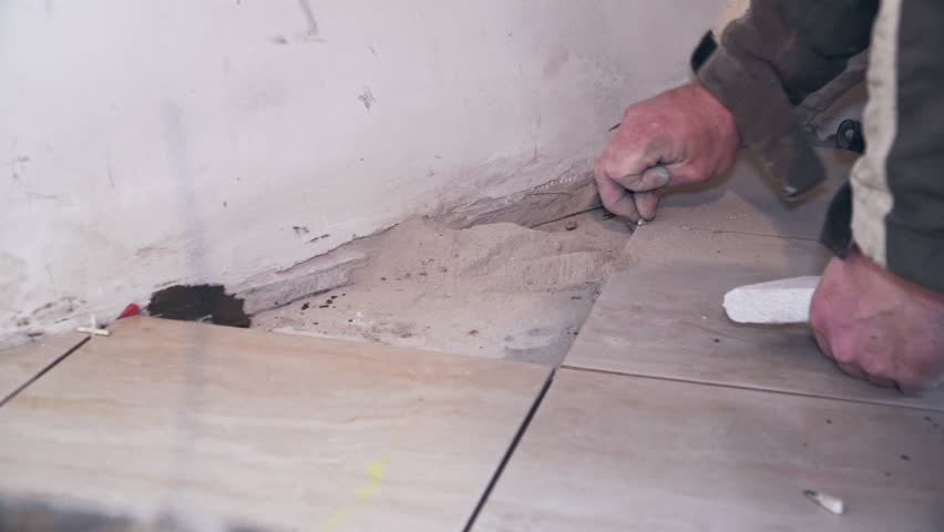 The tiler lays tiles on the floor close up | Shutterstock HD Video #1025098493