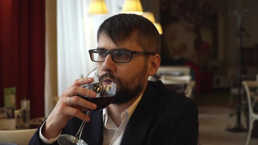 Young attractive man drinks red wine from a glass in a cafe #1025144873