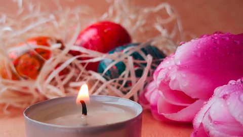 Happy Easter concept, background for a greeting card: closeup burning tea light candle and spring flowers (pink tulips), colorful Easter eggs in the straw in the background