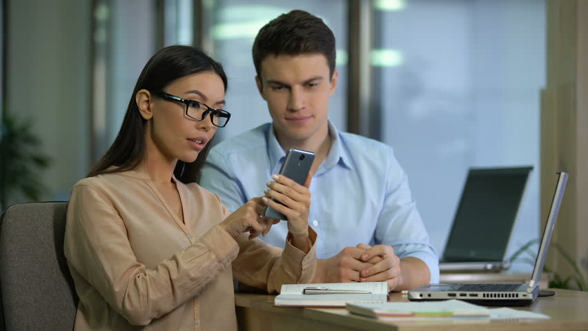 Happy asian caucasian colleagues checking mail on gadget, surprised by good news | Shutterstock HD Video #1025164223