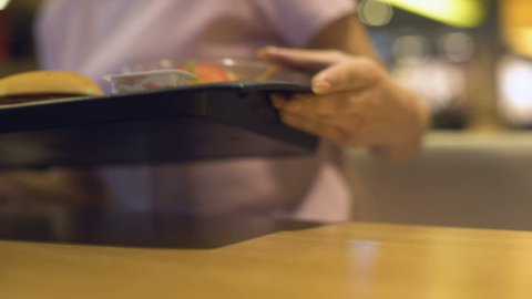 Woman with plastic tray sitting at cafe table, self-service restaurant, canteen