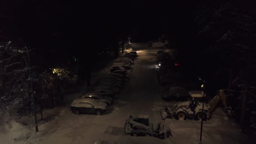 Snow-covered parking in forest. Clip. Top view of parking with snow-covered cars and standing bulldozers to clean snow on background of forest at night