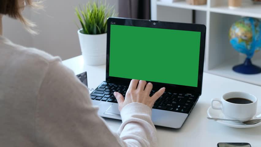 Woman working on a computer, green screen. Over the shoulder shot | Shutterstock HD Video #1025260733