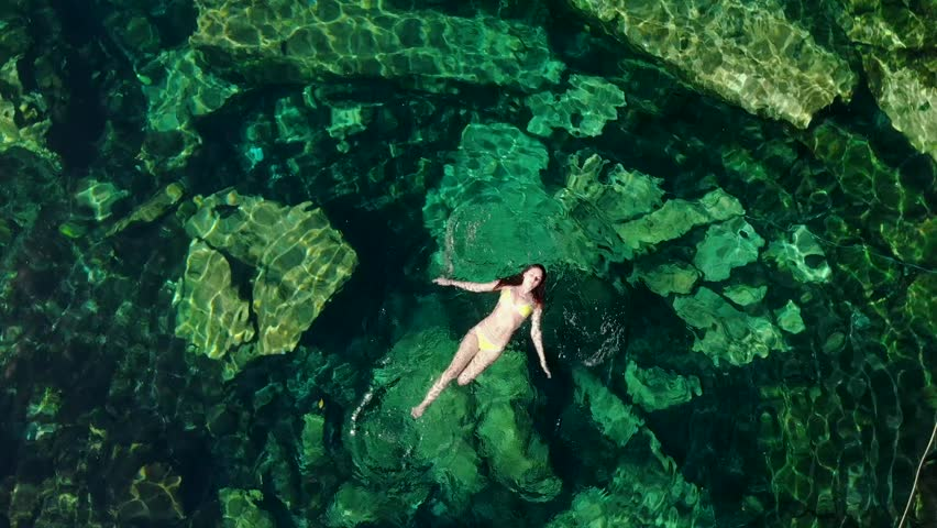 Young brunette woman floats and plays in a natural pool of a cenote in Mexico. | Shutterstock HD Video #1025299283