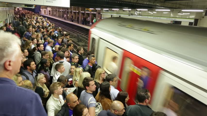 LONDON - CIRCA SEPTEMBER 2014, Busy London underground subway train station time-lapse. Platform and stairs packed with people train arrives, doors open and the crowds move to board train, doors close