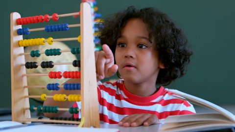 Front view of African American schoolboy learning mathematics with abacus at desk in a classroom. He is counting beads 4k