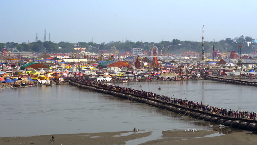 Hindu pilgrims crossing pontoon bridge over the Ganges river at the 2019 Kumbh Mela Festival, the world's largest religious gathering, in Allahabad (Prayagraj), Uttar Pradesh, India. | Shutterstock HD Video #1025343143