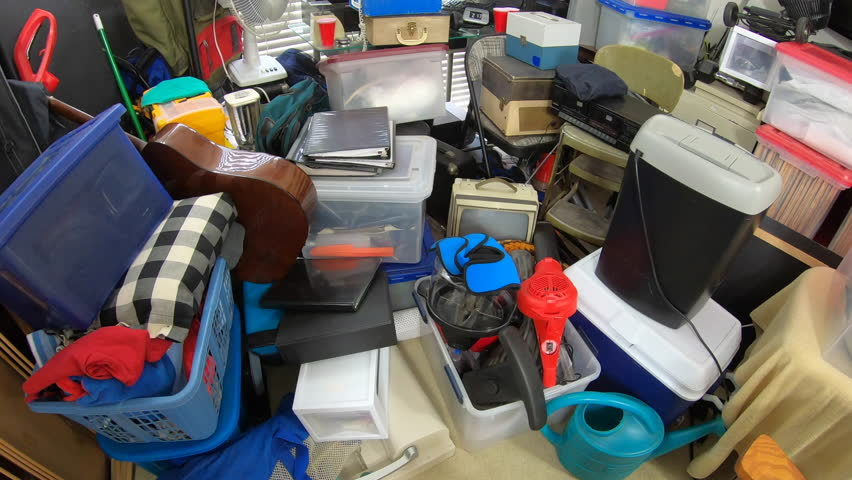 Cluttered hoarder room.  Slow dolly move over piles of household items, vintage electronics, business equipment and miscellaneous junk. | Shutterstock HD Video #1025355533