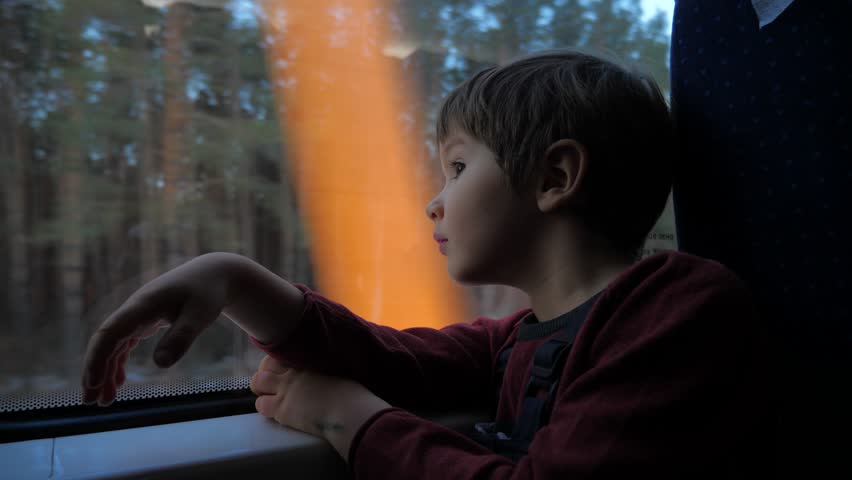 The boy stands at the train window and looks out the window at the running landscapes. Travel by train. Tourism on vacation, travel around the world. Kid traveling by train, dreaming about something. | Shutterstock HD Video #1025359433