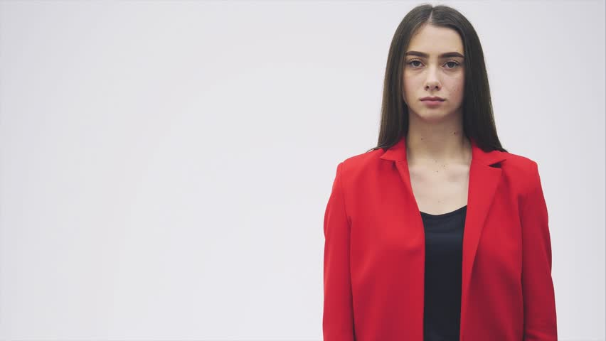 Portrait of a beautiful young brunette. Look into the camera. During this she raised her hand and began to show a gesture of death. Dressed in a red jacket.