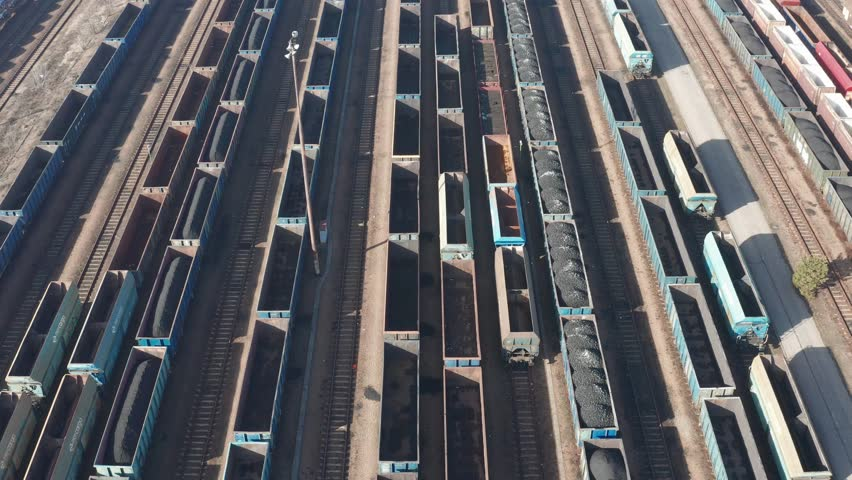 Aerial view of colorful freight trains on the railway station. Wagons with goods on railroad. Heavy industry. Industrial conceptual scene with trains. Top view.