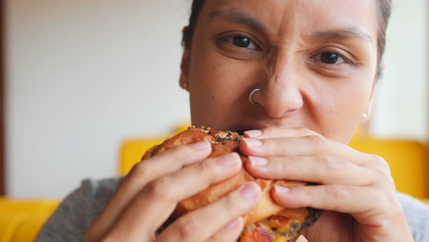 Young Hungry Woman Biting Vegan Meatless Burger in Fast Food Restaurant. Portrait of Angry Face Female Eating and Looking in Camera. 4K Slowmotion.