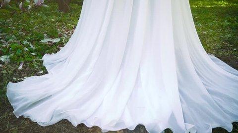 pedestal shot of bride in long white dress in blooming garden
