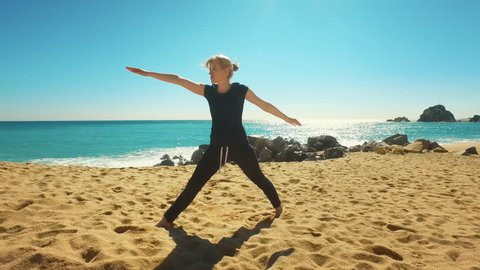 Woman practicing yoga asana on sea beach. Fit girl doing flexibility exercise on sand beach at sunny day. Outdoors yoga practice. Fitness activity on tropical beach