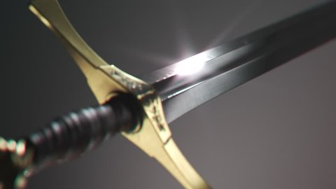 Old vintage medieval sword shining in a bright, white spotlight. Light reflects in a blade symbolizing its sharpness.  Powerful antique weapon polished metal. Camera close up showing intricate details