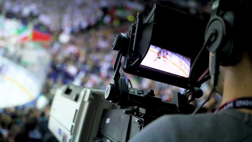 KAZAN, TATARSTAN/RUSSIA - DECEMBER 26 2018: Close backside view young cameraman films hockey game with modern equipment on sports stadium on December 26 in Kazan | Shutterstock HD Video #1025486243