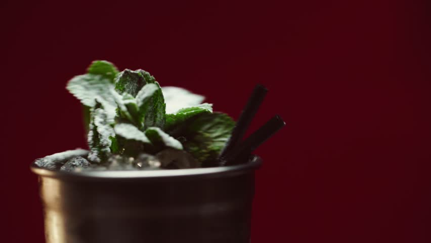 Close up view of mojito cocktail in wet silver glass with mint leaves and ice rotating isolated on burgundy | Shutterstock HD Video #1025544473
