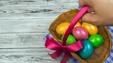 Man puts on a table the Easter basket with Decorated and colored eggs, concept of Christian holiday Pascha or Resurrection Sunday