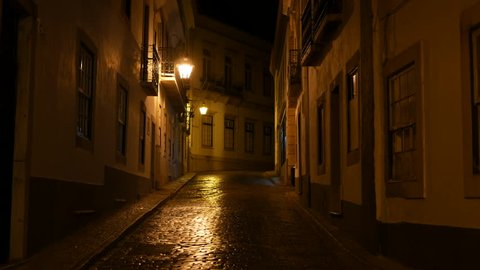 Old town of Faro, Algarve, Portugal at night. Cobblestones street, lit by yellow street lamps. Pan up.